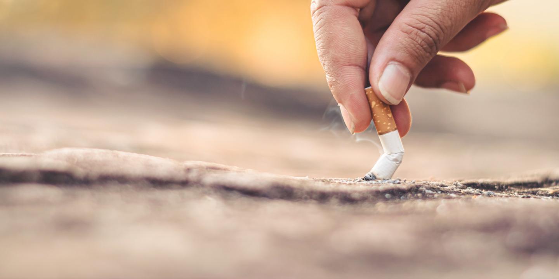 Hand drückt Zigarette auf Boden aus