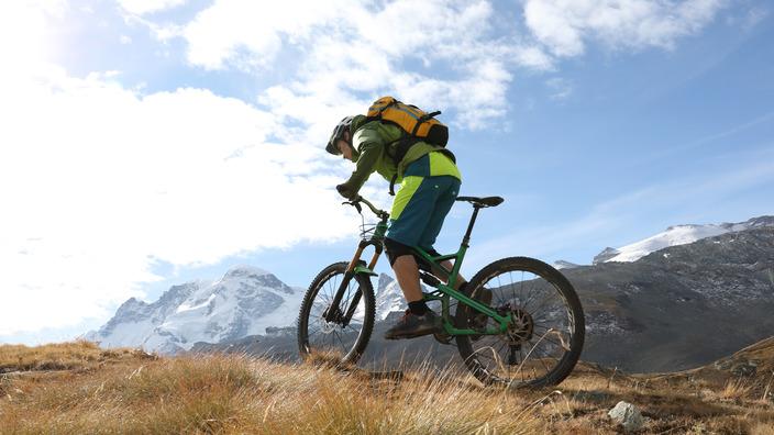 Mann fährt mit Mountainbike den Berg hoch