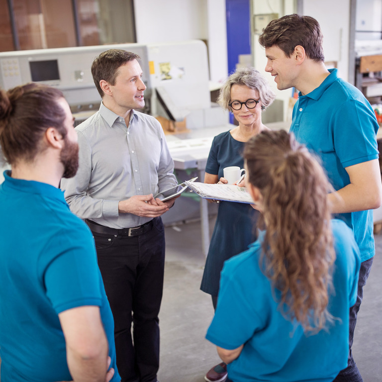 Fünf Mitarbeiter stehen im Kreis und reden in Lagerhalle