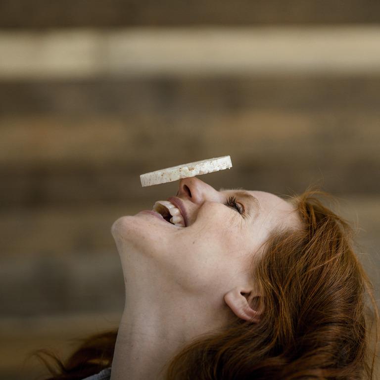Rothaarige junge Frau balanciert eine Reiswaffel auf ihrer Nase