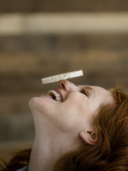Frau balanciert Reiswaffel auf ihrer Nase und lacht