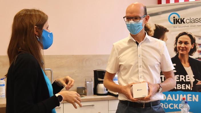 IKK-Gesundheitsmanagerin Maja Miebach übergibt Andreas Nitsch <br/>einen Schrittzähler