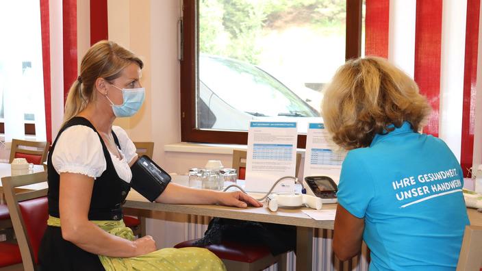 IKK-Gesundheitsmanagerin Petra Heinle misst Blutdruck bei einer Teilnehmerin