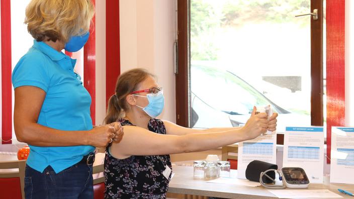 Katharina Meyer zeigt einer Mitarbeiterin eine Übung