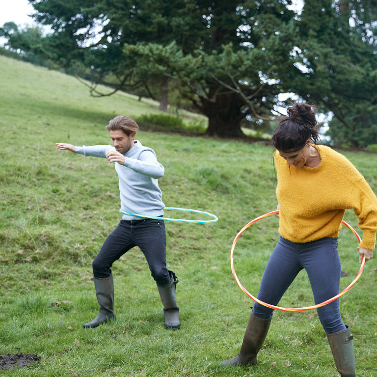 Ein Mann und eine Frau trainieren mit Hula-Hoop-Reifen auf einer Wiese