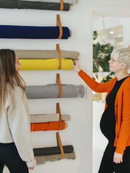 Schwangere Frau berät Kundin zu Stoffmustern.