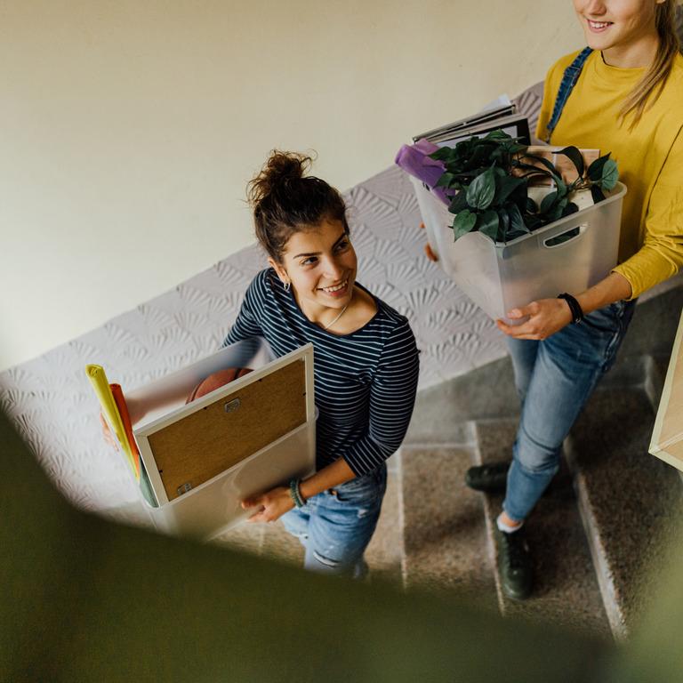 Zwei junge Frauen tragen Umzugskarton eine Treppe hinunter.