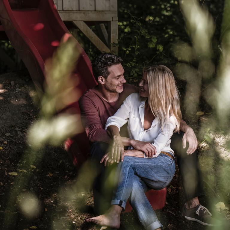 Paar mit Familienwunsch sitzt in der Natur