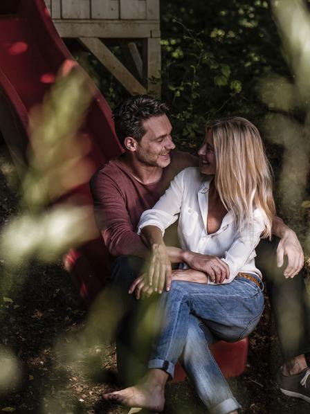 Junge Frau und junger Mann sitzen kuschelnd auf einer Kinderrutsche