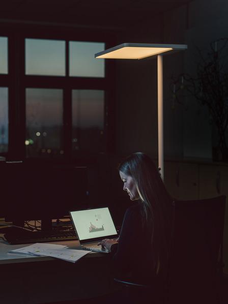 Arbeitnehmerin sitzt spät nachts noch am Schreibtisch und arbeitet