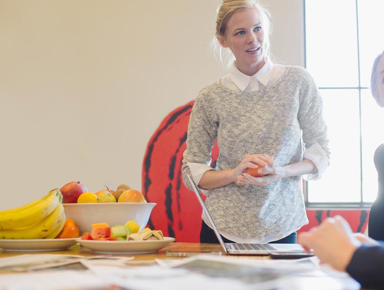Frauen sprechen auf Arbeit über gesunde Ernährung, Bananen und anderes Obst liegt auf dem Tisch.