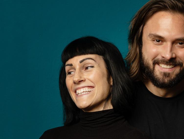 Achim und Verena Sam lächelnd vor einem dunklen Hintergrund