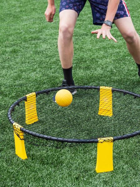 Person spielt Spikeball auf dem Rasen