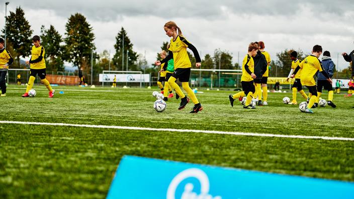 Gruppe Fußballkids in BVB-Outfits trainiert auf dem Rasen, im Vordergrund das IKK classic-Logo