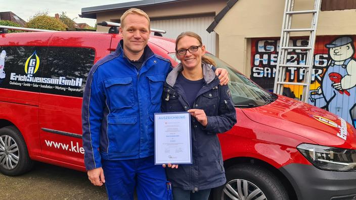 Ole und Katja Svensson mit der Urkunde vor dem Firmenwagen