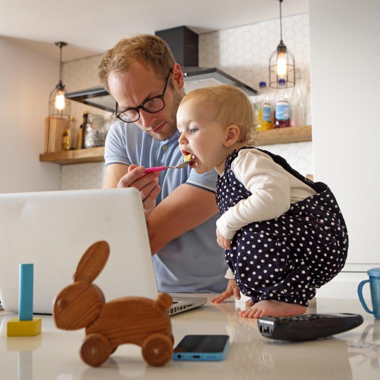 Vater füttert seinen kleinen Sohn und arbeitet gleichzeitig an seinem Laptop