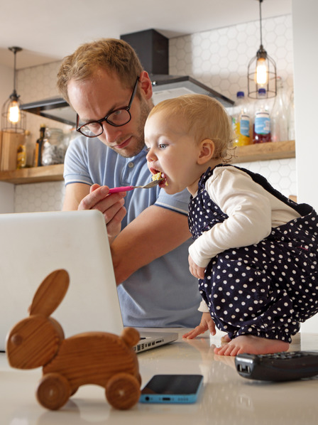 Mann füttert Kind und arbeitet gleichzeitig am Laptop.