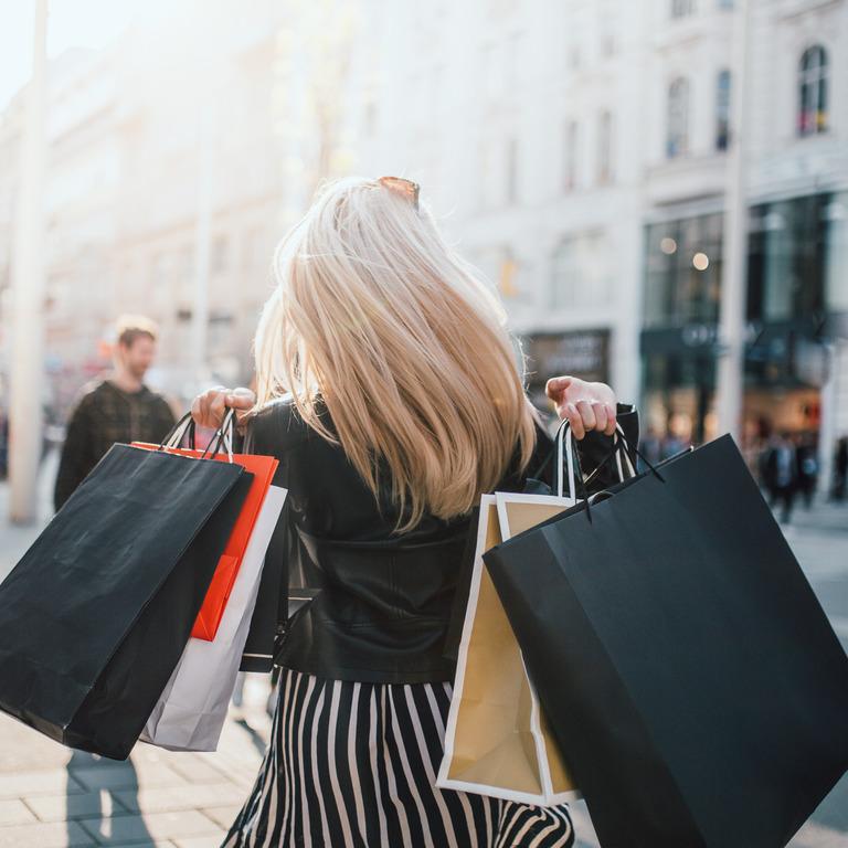 Frau mit vielen Einkaufstüten geht in der Stadt shoppen.