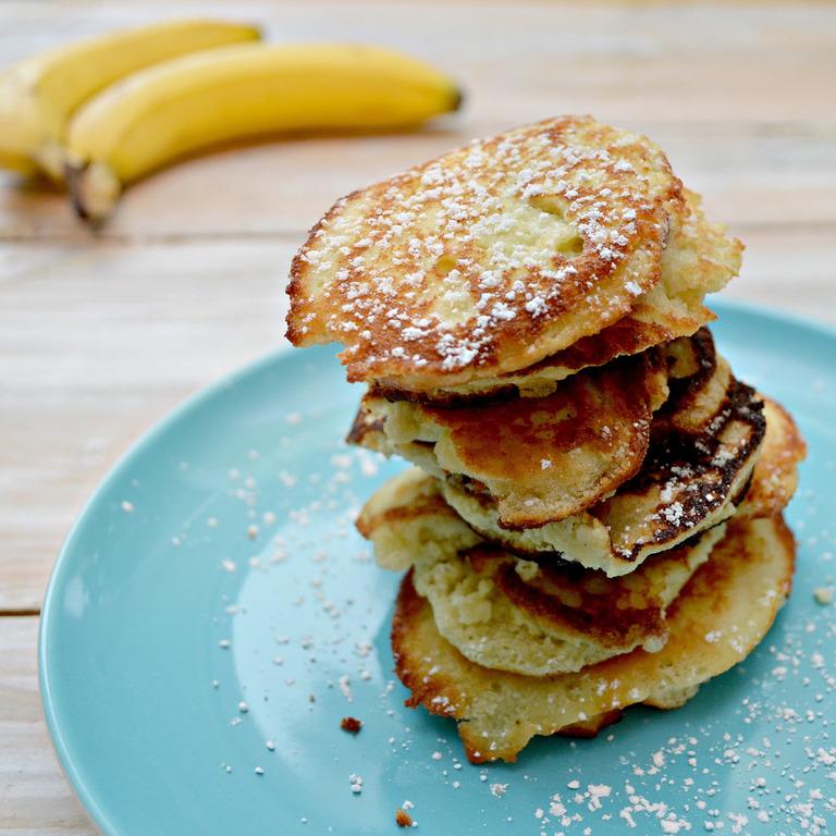 Ein Teller mit Bananen-Pancakes und Bananen im Hintergrund.