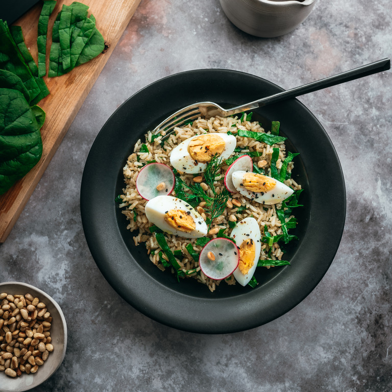 Reis-Bowl mit Spinat und Ei in einer schwarzen Schüssel.