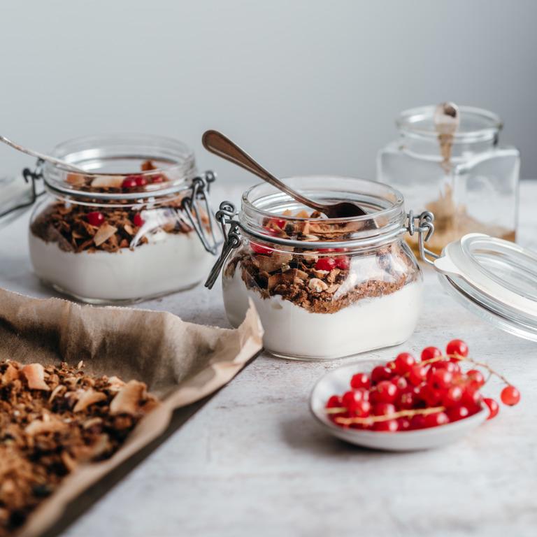 Aus altem Vollkornbrot gebackenes Müsli mit Joghurt und Beeren im Glas.