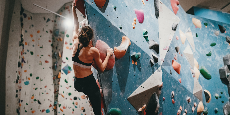 Frau klettert in Boulderhalle