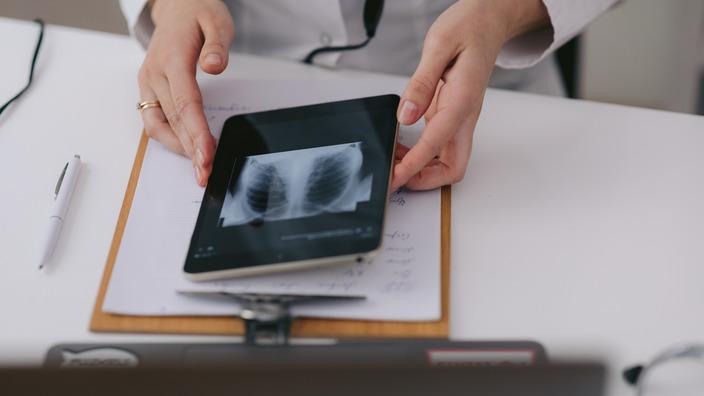 Händepaar hält ein Tablet, auf dem ein Röntgenbild zu sehen ist