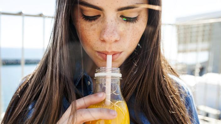 Junge Frau mit langen braunen Haaren trinkt ein isotonisches Getränk aus der Flasche mit einem Strohhalm