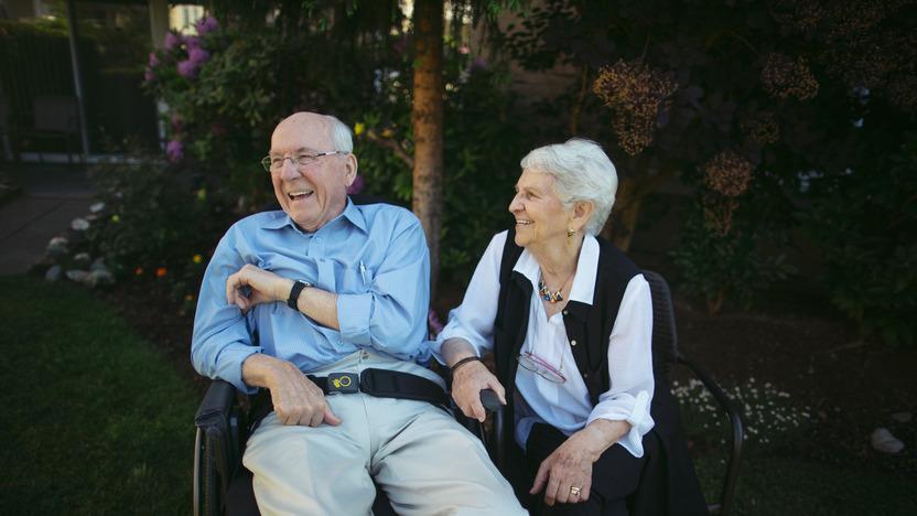 Älterer Mann sitzt lachend im Rollstuhl, daneben sitzt eine ältere Frau