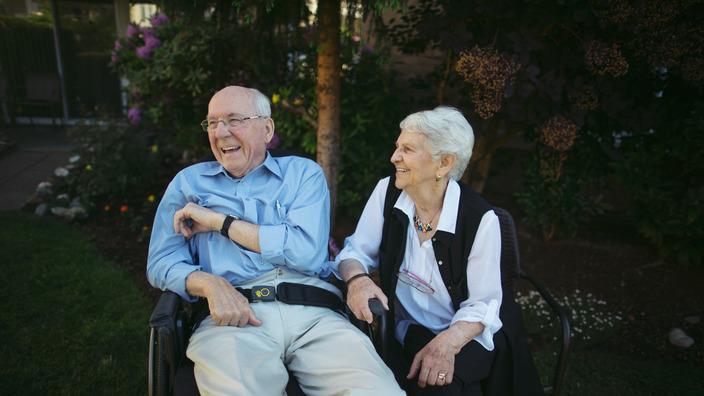 Seniorin und ihr pflegebedürftiger Mann sitzen gut gelaunt im Garten