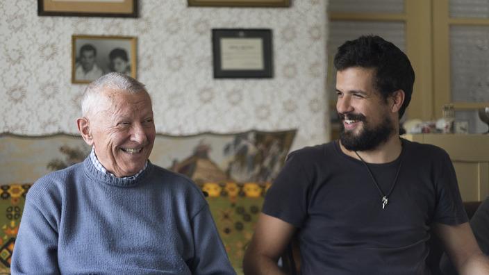 Senior und junger Mann sitzen gemeinsam am Esstisch