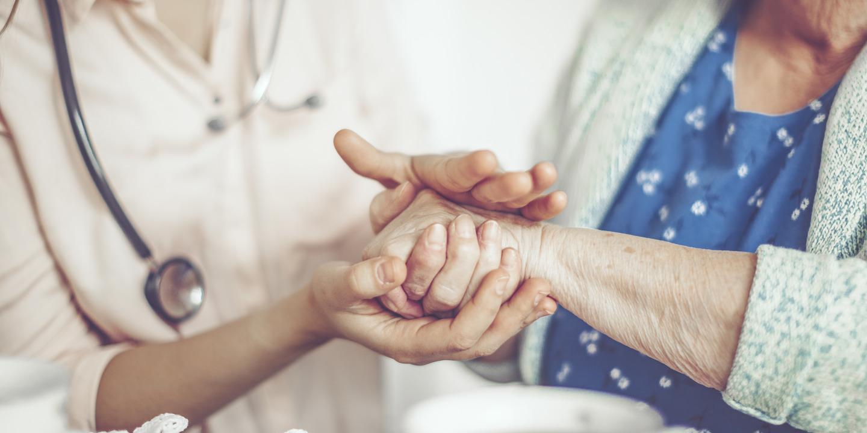 Pflegerin cremt einer Seniorin die Hände ein