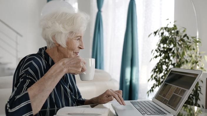 Seniorin sitzt mit einer Tasse Kaffee an ihrem Laptop