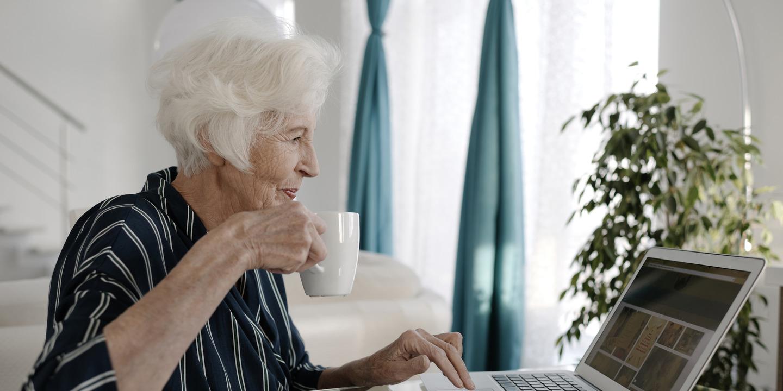 Seniorin sitzt mit einer Tasse Tee vor dem Laptop und prüft ihre Unterlagen