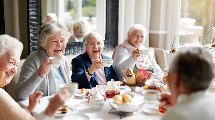 gut gelaunte Gruppe Seniorinnen an einer Kaffeetafel