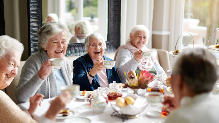 gut gelaunte Seniorinnen sitzen an einer Kaffeetafel