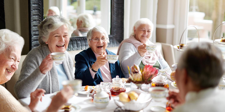 gut gelaunte Gruppe Seniorinnen sitzt an einer Kaffeetafel