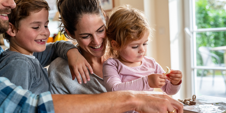 Eltern kochen mit ihrem kleinen Sohn und ihrer kleinen Tochter in der Küche.