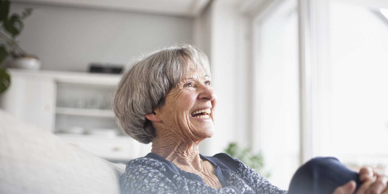 Seniorin sitzt gut gelaunt auf ihrer Couch