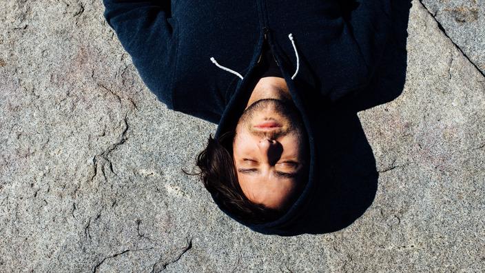 junger Mann mit Kopfschmerzen liegt mit geschlossenen Augen auf dem Boden