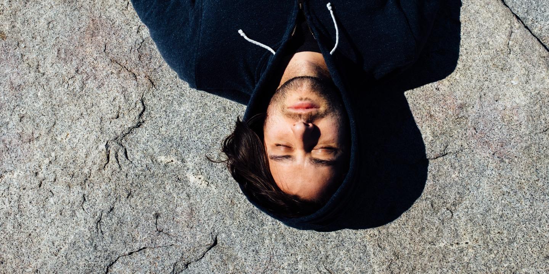 Junger Mann mit Kopfschmerzen liegt mit geschlossenen Augen auf dem Rücken.