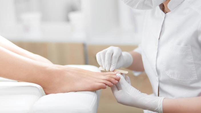 Podologin behandelt den Fuß einer Diabetikerin