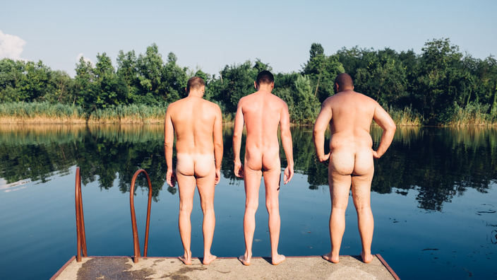 drei nackte Männer stehen am Rand eines Badesees und blicken hinein