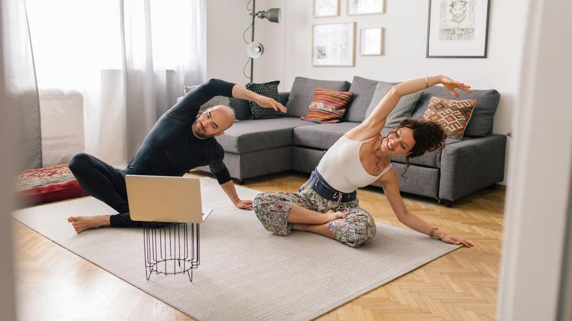 Zwei Menschen machen Sport in der Wohnung vor einem Laptop.