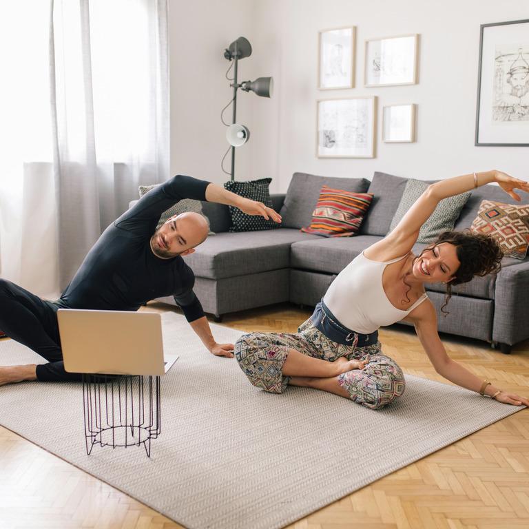 Paar macht Sport im Wohnzimmer vor dem Laptop