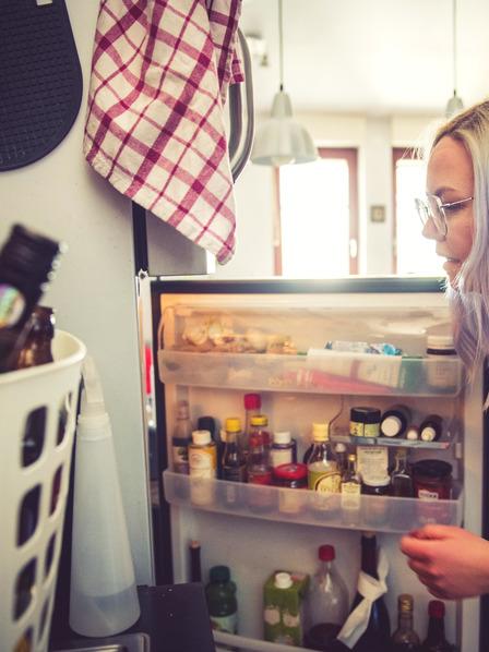 Frau steht vor offenem Kühlschrank und guckt rein