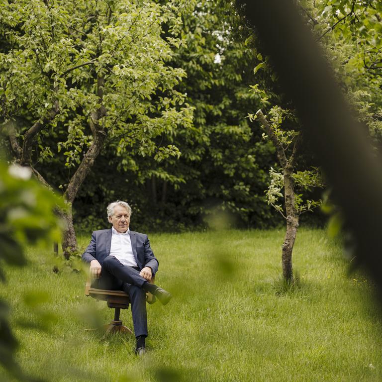 Weißhaariger Herr im Anzug sitzt auf Stuhl im Garten.