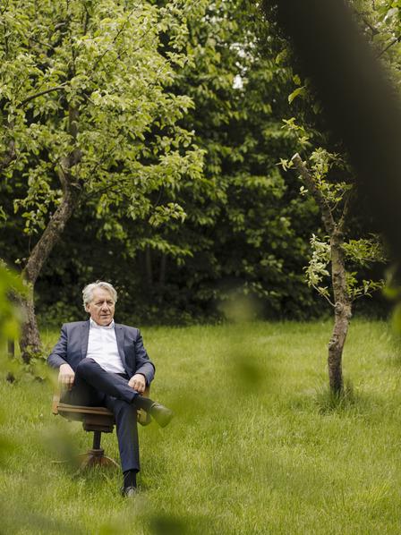 Mann sitz auf einem Stuhl auf einer Wiese