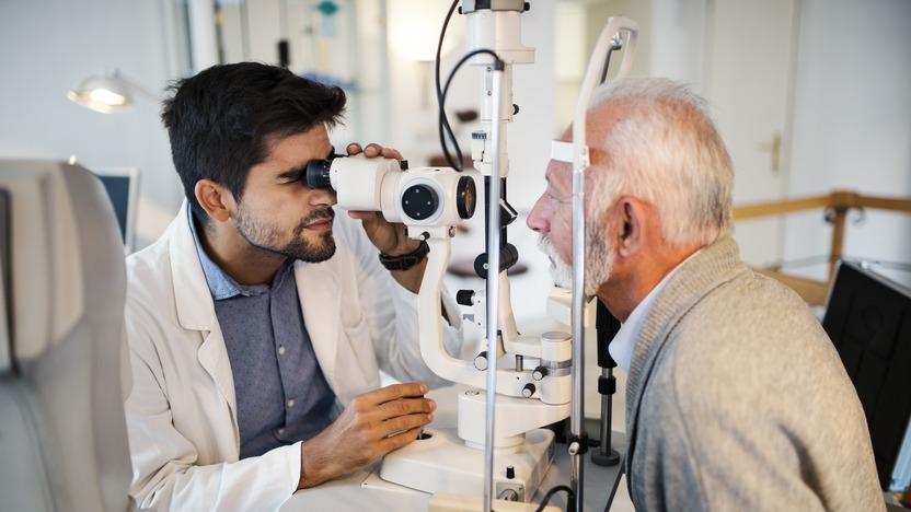 Älterer Mann lässt sich beim Augenarzt am Messgerät untersuchen.