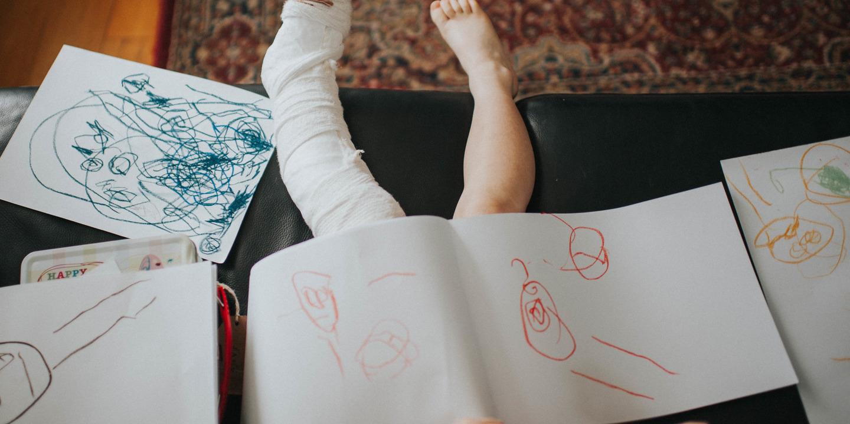 Junge mit eingegipstem Bein malt in Buch.